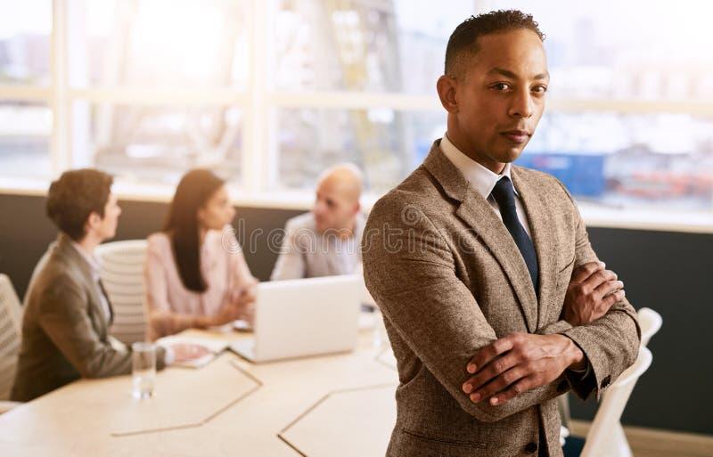 Homme d'affaires se tenant devant ses employés avec les bras croisés photos libres de droits