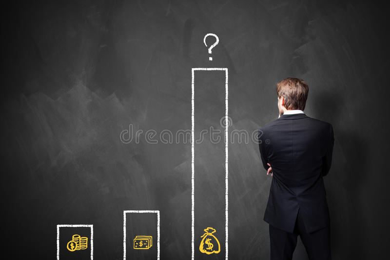 Homme d'affaires se tenant devant un tableau noir avec un diagramme au sujet de différents types de salaires photographie stock libre de droits