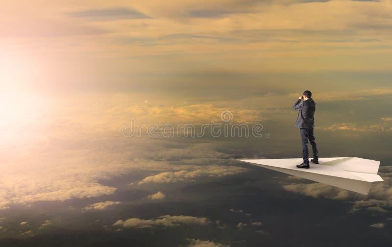 Homme d'affaires se tenant et remarquant binoculaire sur des agains d'avion de papet images stock
