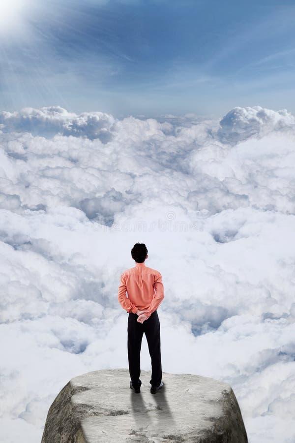 Homme d'affaires se tenant sur la crête de montagne photos stock