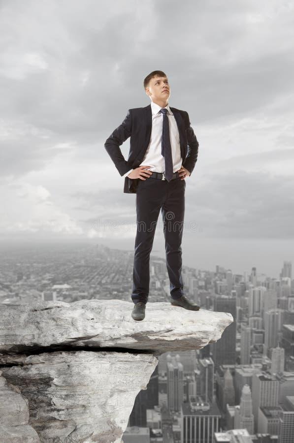 Homme d'affaires se tenant sur une crête photographie stock libre de droits
