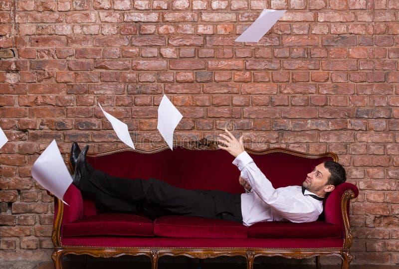 Homme d'affaires se trouvant sur un canapé avec des papiers de vol images libres de droits