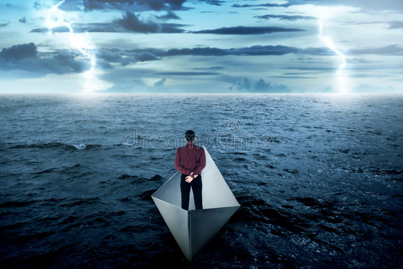 Homme d'affaires seul se tenant sur le bateau de papier image stock