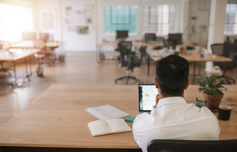 Homme d'affaires seul travaillant dans un grand bureau moderne photos stock