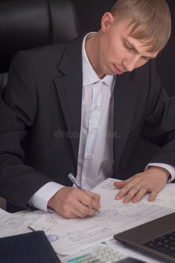 Homme d'affaires signant un contrat Le directeur r?dige le rapport et compl?te la d?claration Homme d'affaires au travail dans so photo libre de droits