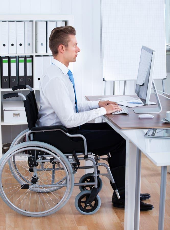 Homme d'affaires Sitting On Wheelchair et ordinateur d'utilisation photographie stock