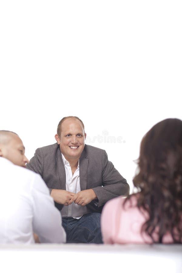 Homme d'affaires Smiling In Front Of Two Colleague photo libre de droits