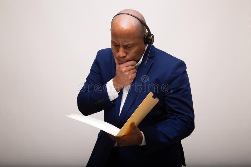 Homme d'affaires songeur Looks Through File d'Afro-américain photographie stock