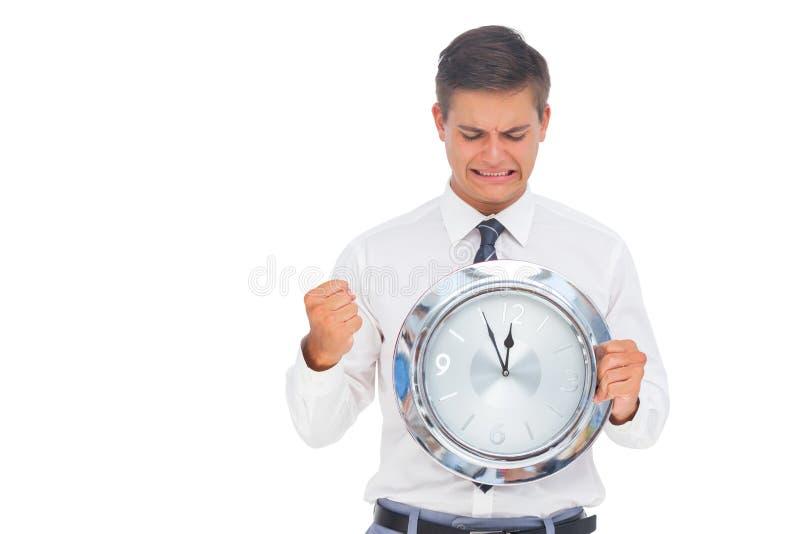 Homme d'affaires soucieux tenant et regardant l'horloge photographie stock libre de droits