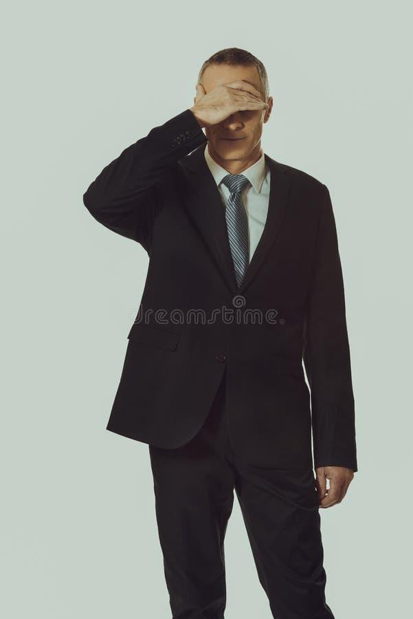 Homme d'affaires soumis à une contrainte couvrant son visage photos stock