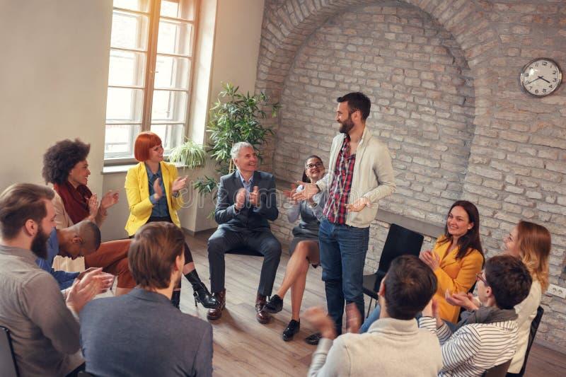 Homme d'affaires souriant dans des collègues de réunion de groupe applaudissant en le GR photo libre de droits