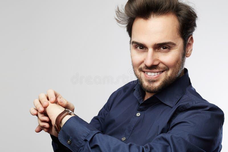 Homme d'affaires souriant et regardant sa montre D'isolement sur un fond gris photos libres de droits