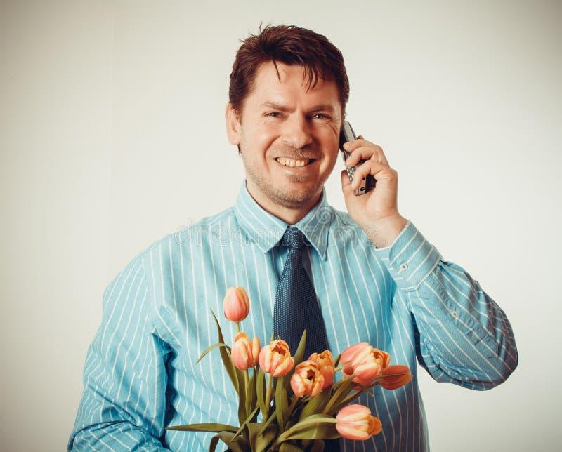 Homme d'affaires souriant tout en téléphonant et tenant des tulipes images libres de droits