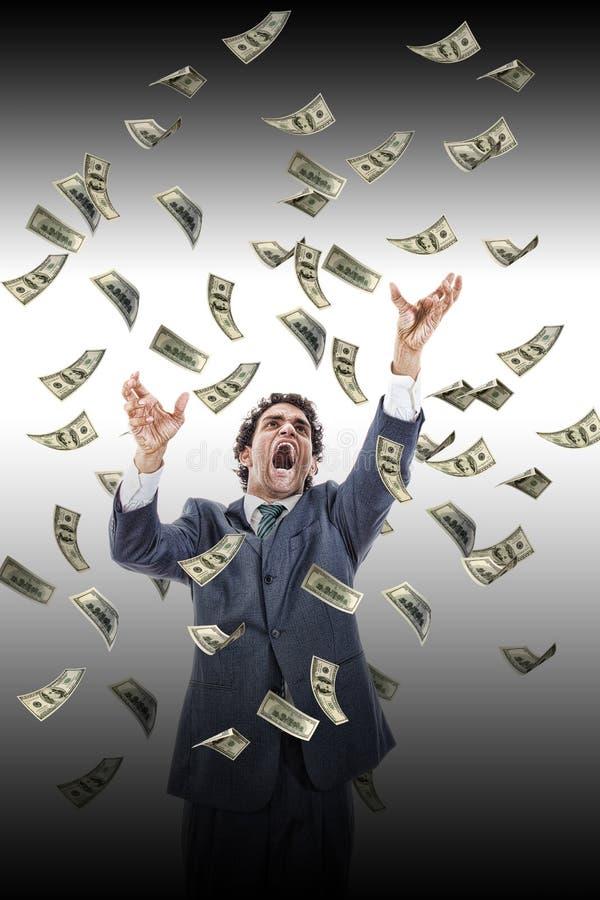 Homme d'affaires sous les billets de banque en baisse d'argent criant atteignant les FO images stock