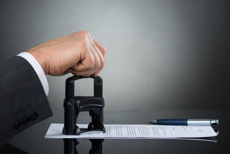 Homme d'affaires Stamping Contract Document au bureau photos stock