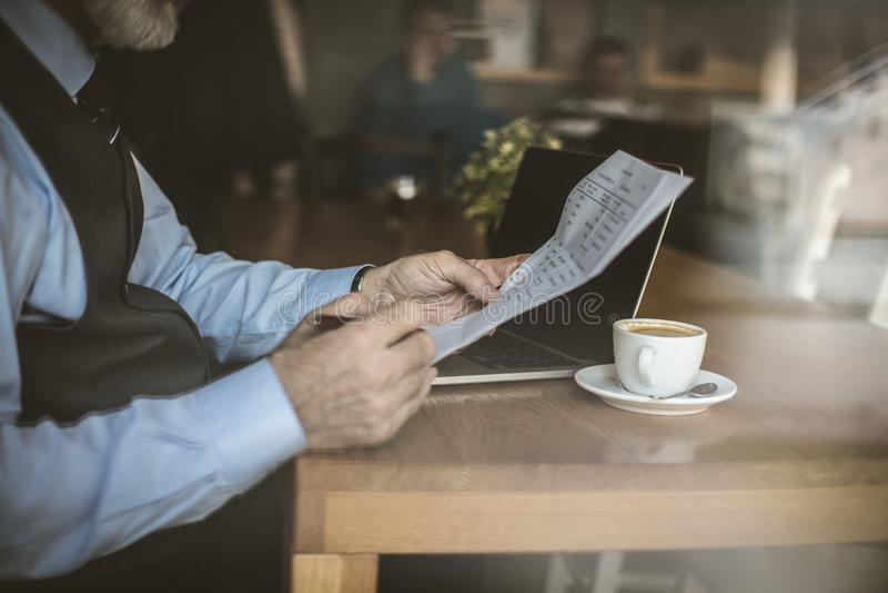 Homme d'affaires supérieur au café travaillant sur son ordinateur portable photographie stock