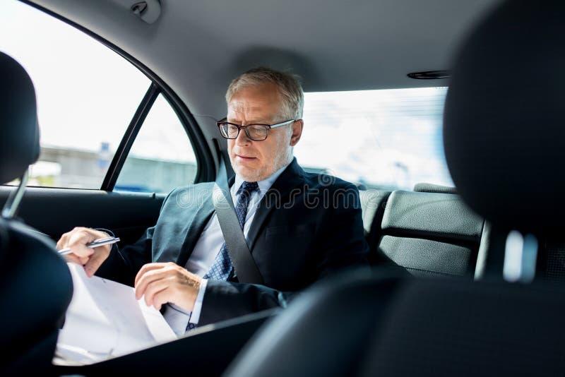 Homme d'affaires supérieur avec des papiers conduisant dans la voiture photographie stock libre de droits