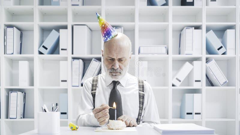 Homme d'affaires supérieur ayant un anniversaire isolé triste image stock