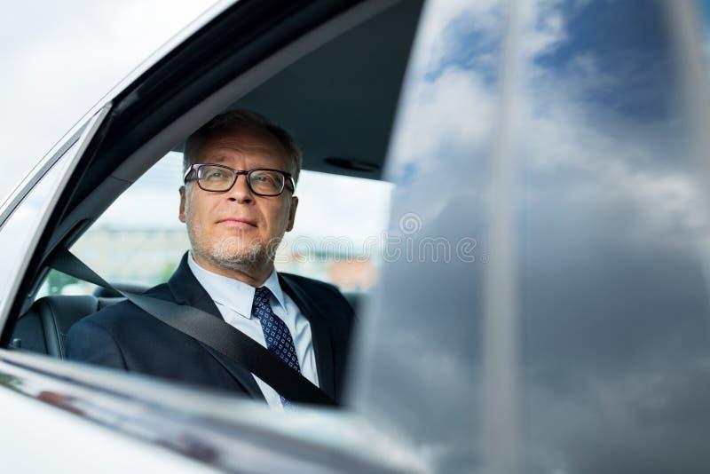 Homme d'affaires supérieur conduisant sur le siège arrière de voiture image stock
