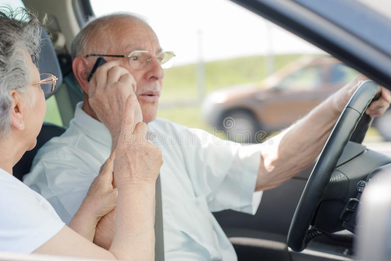 Homme d'affaires supérieur conduisant tout en à l'aide du téléphone images libres de droits