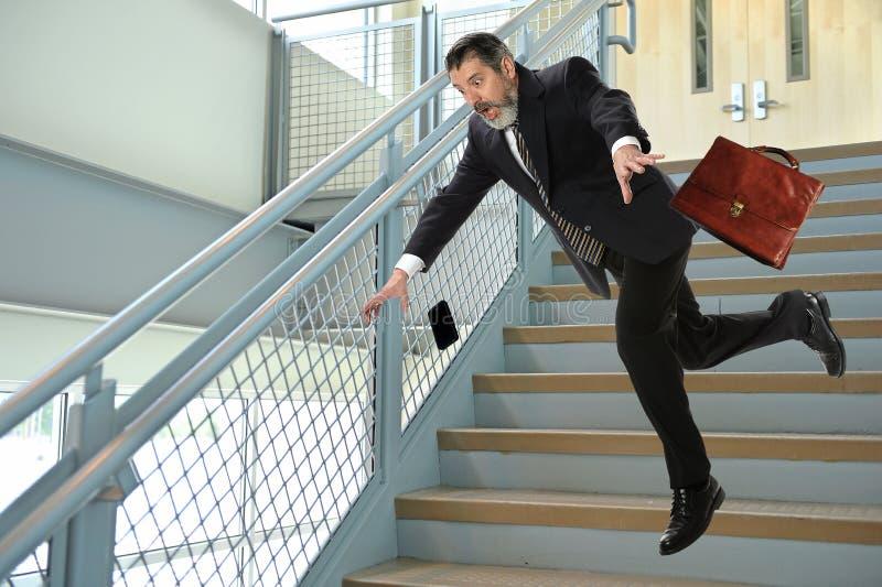 Homme d'affaires supérieur Falling sur des escaliers photographie stock libre de droits