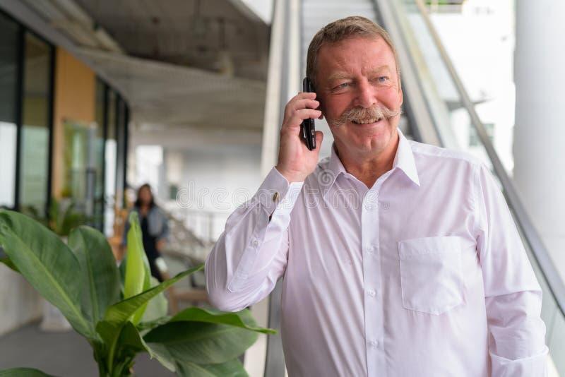 Homme d'affaires supérieur heureux pensant tout en parlant au téléphone dans la ville photographie stock
