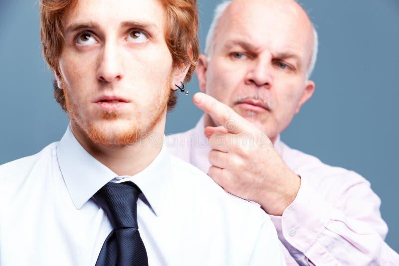 Homme d'affaires supérieur indiquant une boucle d'oreille de travailleurs photographie stock