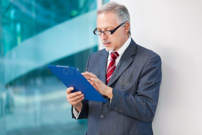 Homme d'affaires supérieur lisant un document image stock