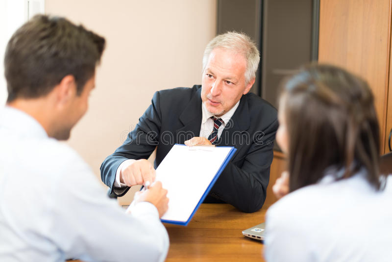 Homme d'affaires supérieur montrant un document pour signer à un couple : Signature de document images stock