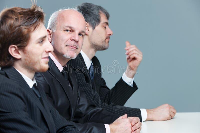 Homme d'affaires supérieur réfléchi lors d'une réunion photo libre de droits
