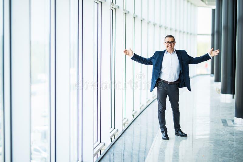 Homme d'affaires supérieur réussi avec les mains augmentées sur le bureau moderne photo libre de droits