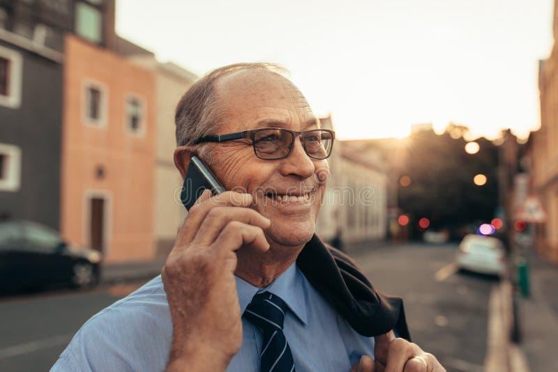 Homme d'affaires supérieur sur la rue de ville utilisant le téléphone images libres de droits