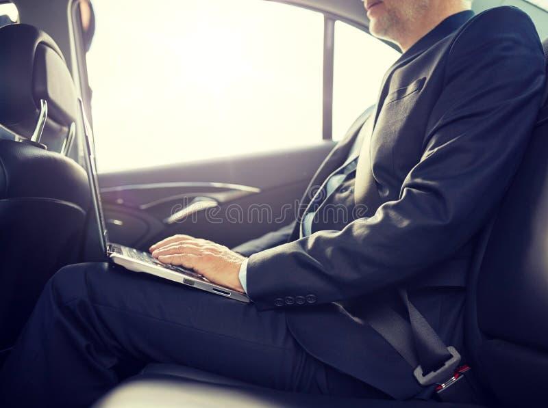 Homme d'affaires sup?rieur avec l'ordinateur portable conduisant dans la voiture images libres de droits