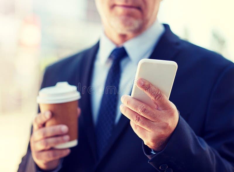 Homme d'affaires sup?rieur avec le smartphone et le caf? photos libres de droits