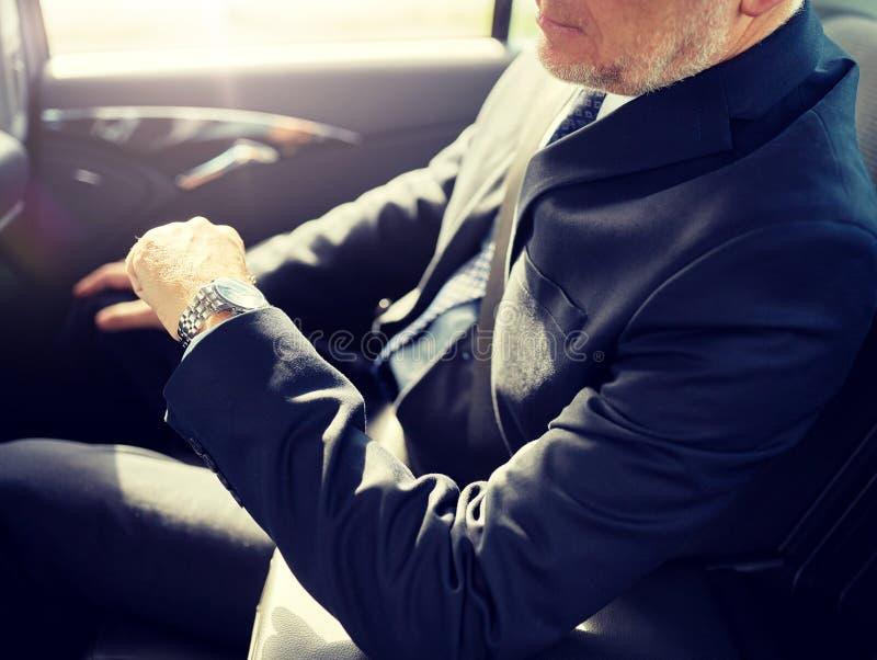 Homme d'affaires sup?rieur conduisant sur le si?ge arri?re de voiture photographie stock