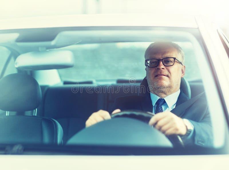 Homme d'affaires sup?rieur heureux conduisant la voiture image stock