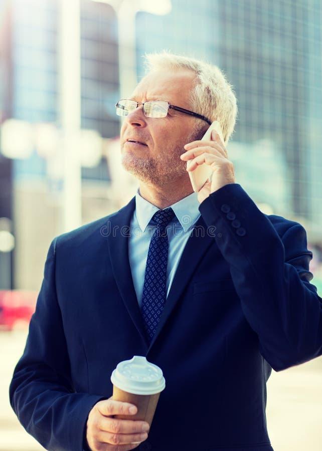 Homme d'affaires sup?rieur invitant le smartphone dans la ville images stock