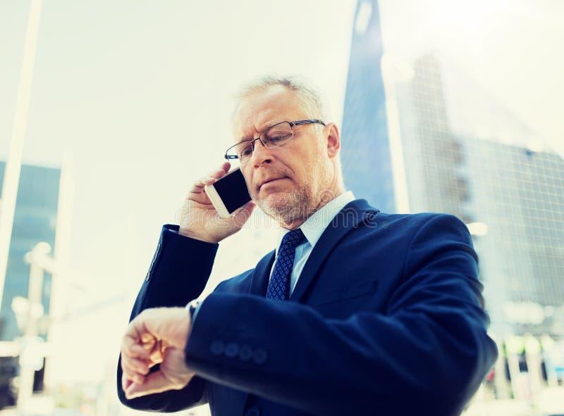 Homme d'affaires sup?rieur invitant le smartphone dans la ville photo libre de droits
