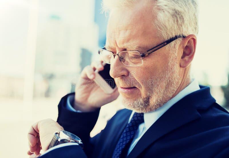 Homme d'affaires sup?rieur invitant le smartphone dans la ville photos libres de droits
