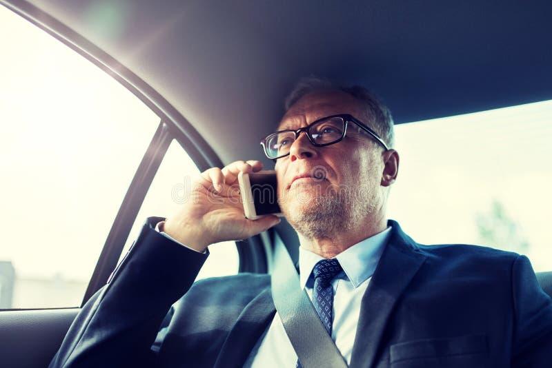 Homme d'affaires sup?rieur invitant le smartphone dans la voiture images libres de droits