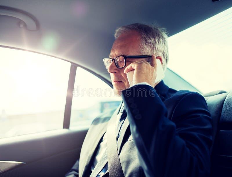 Homme d'affaires sup?rieur invitant le smartphone dans la voiture images stock