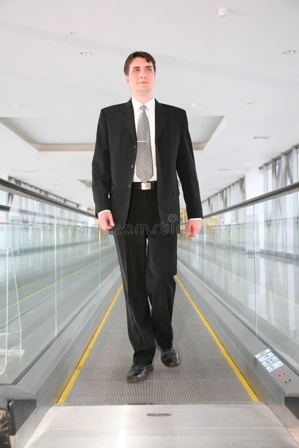 Homme d'affaires sur l'escalator photographie stock libre de droits