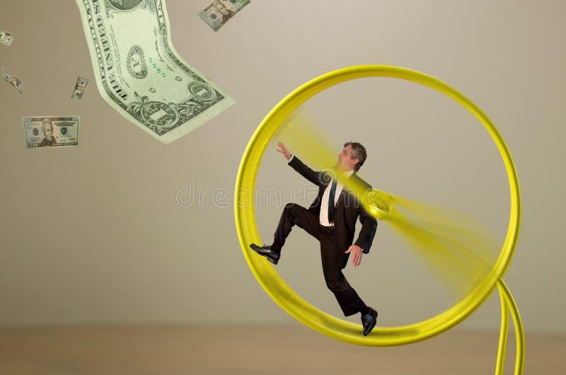 Homme d'affaires sur la roue de hamster chassant le succès d'argent photographie stock libre de droits