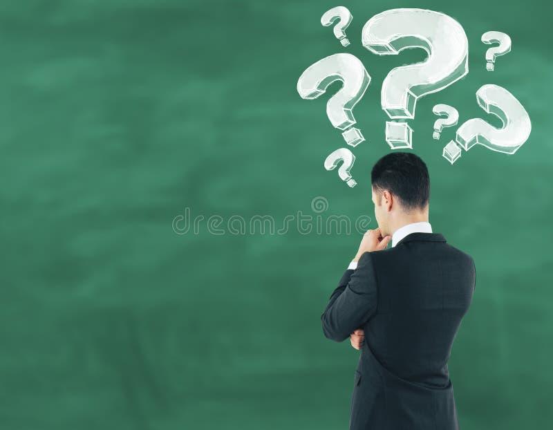Homme d'affaires sur le fond de tableau regardant la question tirée m photographie stock