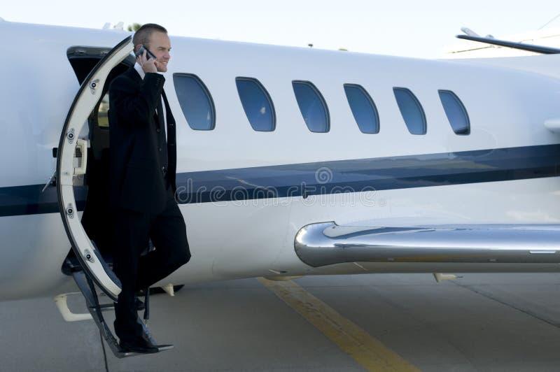 Homme d'affaires sur le téléphone portable quittant l'avion à réaction de corporation photographie stock libre de droits