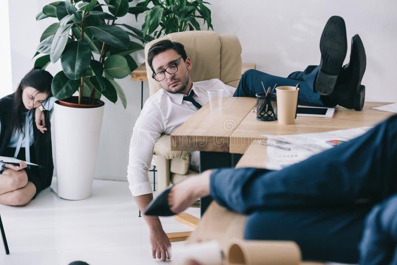 homme d'affaires surchargé dormant au bureau avec des pieds images libres de droits