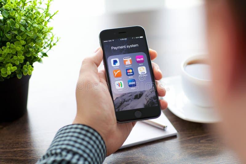 Homme d'affaires tenant l'iPhone 6 avec un ensemble de système de paiement photographie stock