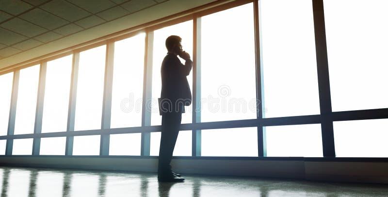 Homme d'affaires tenant la fenêtre proche de bureau et parlant sur le pH mobile images libres de droits