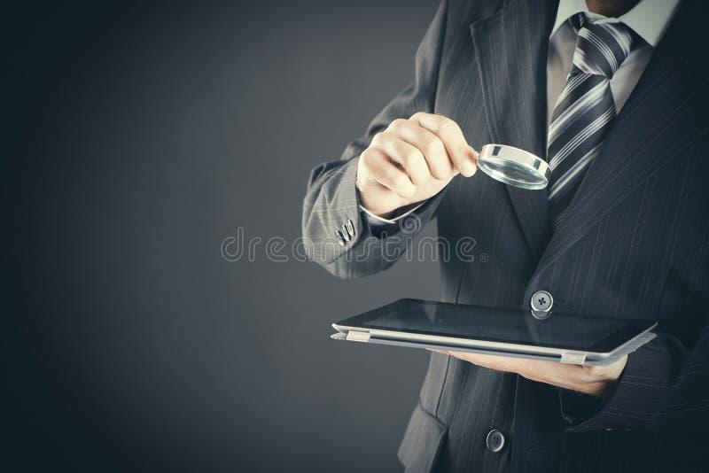 Homme d'affaires tenant la loupe et le comprimé numérique sur le concept de fond, de recherche et d'examen foncé photos libres de droits