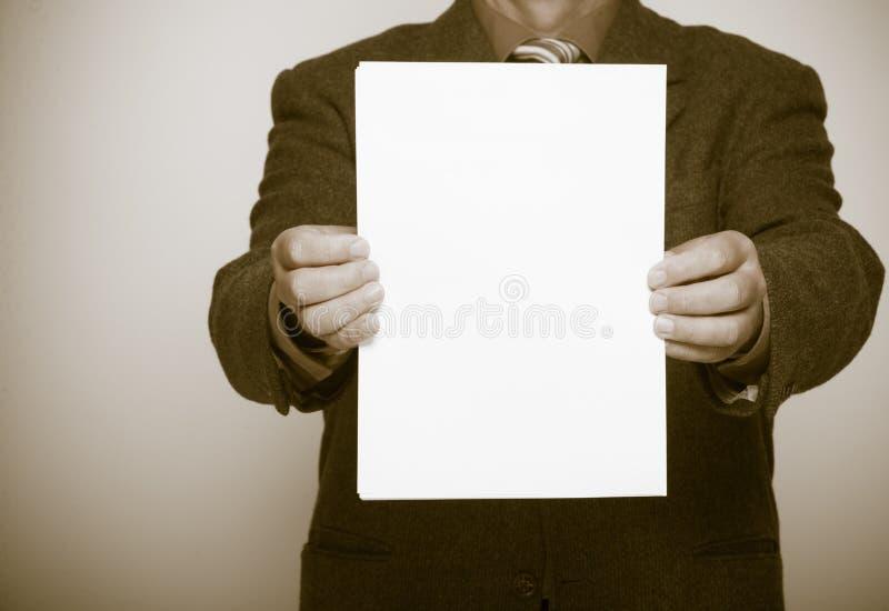Homme d'affaires tenant la page du papier blanche. Concept d'affaires. photographie stock